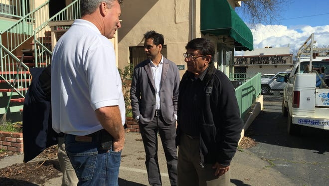 Vijay Soni, right, who bought the former Redding Inn, talks to Alex Gabel of Gabel's Hauling & Demolition, left, as Ponderosa Inn owner Sam Sekhon, center, looks on in February.
