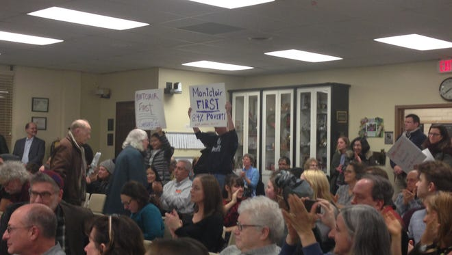 """Audience members hold signs reading """"Montclair First"""" during the Feb. 21 Township Council meeting."""