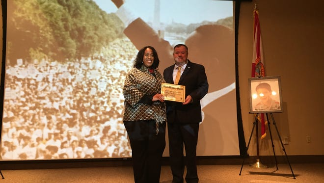 TaMaryn Waters, left, accepts her award from DCF Secretary Mike Carroll.