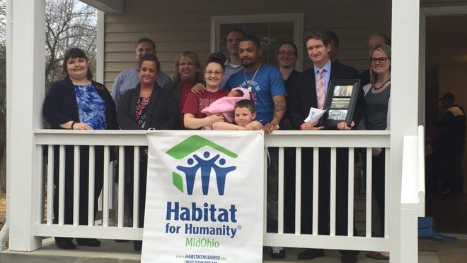 Brooke Filkins and her family take a photo with Park National Bank employees in front of her new home.
