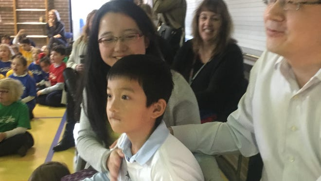 Kindergartner Marcus Zheng with his mom, Cathy Guo, and his dad, Yi Zheng, following the reveal.