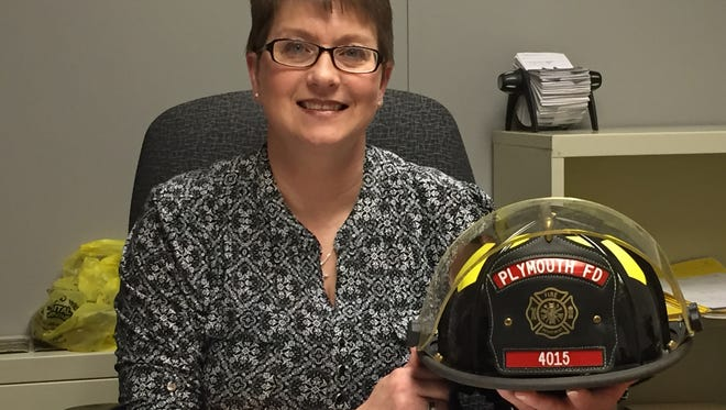 Jamie Akers sits in her office at the Richland County Prosecutor's Office with a fire helmet from her other job.