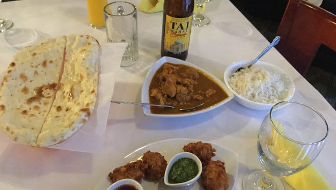 Shahi Palace offerings include the mango lassi drink and (clockwise from top left) naan, a traditional white flour bread; chicken curry; basmati rice; and the vegetable pakora appetizer served with tamarind and mint chutney.