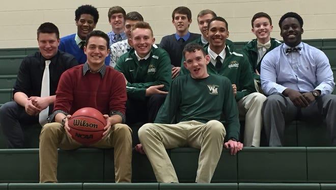 Basketball manager McGregor Long, front right, sits with the Wilson Memorial team before a game late in the season. Long, part of the school's exceptional learners program, earned a varsity letter this season.