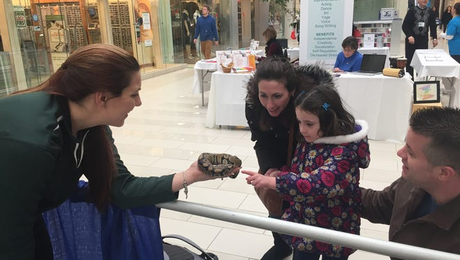 """Jessica Santiago, owner of Two by Two Zoo in LaGrange, holds a ball python snake as Hayley Napoleon of Highland touches it. Hayley's parents, Brian and Elyssa Napoleon, look on. All four were at the Poughkeepsie Galleria Saturday for """"Abilities First: A Showcase of Resources for Enrichment & Inclusion."""""""