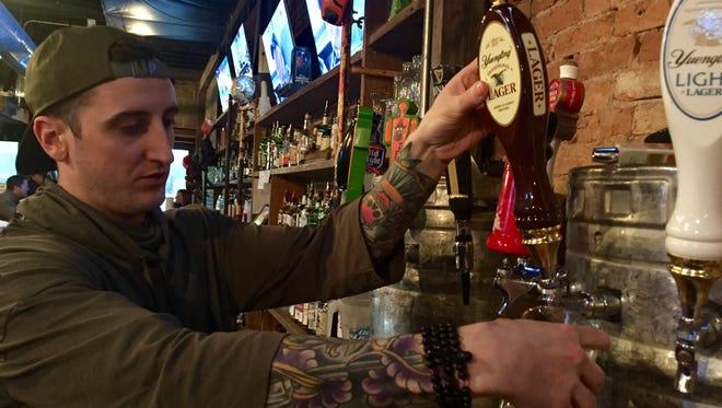 Skylar Redmon, a bar tender at DT Kirby's, pours a Yuengling pint.