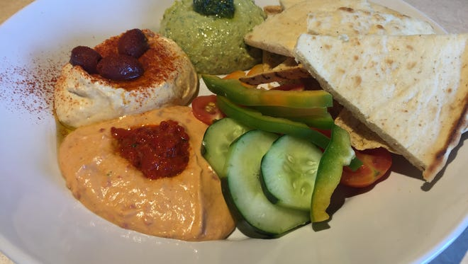 The Hummus Trio features basil-pesto, red peper and classic hummus served with pita chips, cucumbers, bell peppers and cherry tomatoes.