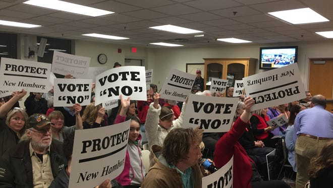 New Hamburg residents hold up signs urging the Poughkeepsie town board to reject a settlement agreement with Bottini Fuel Co. over truck traffic restrictions in the hamlet on Wednesday, March 8, 2017.