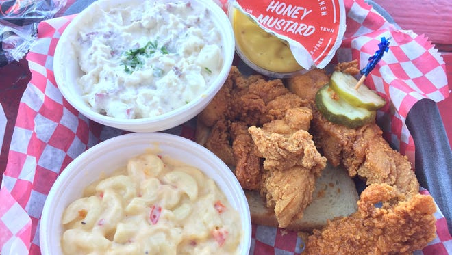 Three jumbo mild tenders on the plate from Hattie B's hot chicken includes two sides. Here, sides are potato salad and mac and pimento cheese.