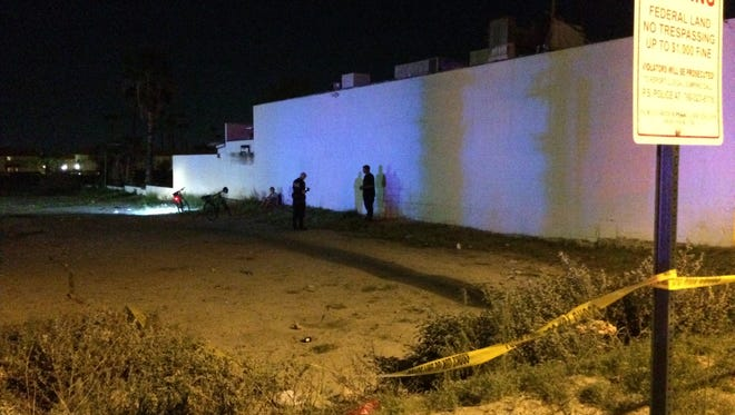 Palm Springs police search for evidence in a vacant lot in the 400 block of South Indian Canyon Drive Thursday after two people were shot. Police were also continuing to search for the shooter.