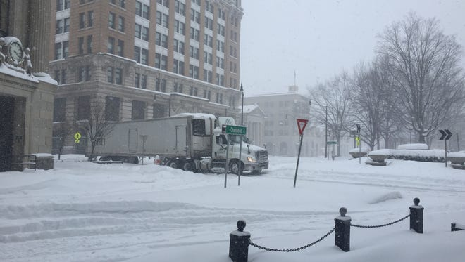 A tractor-trailer at the intersection of Court Street and Chenango Street by a roundabout in downtown Binghamton was stuck in snow during the winter storm.