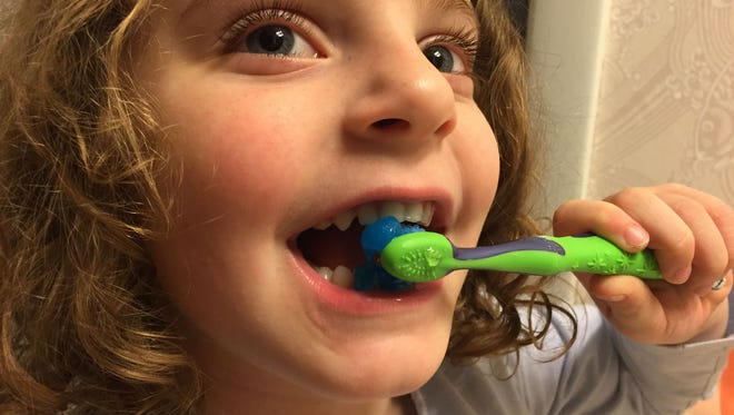 There is too much toothpaste on this 5-year-old's brush.