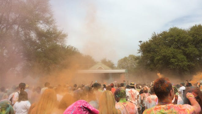 Revelers coat one another in colored powder during the sixth Lafayette Holi Festival in  2016.