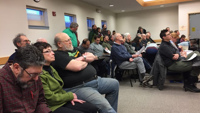 People listen during a public hearing on a solar farm project in Dryden on Thursday, March 16.