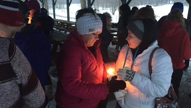 Loved ones of Kaitlyn Carroll-Peak take part in a candlelight vigil Friday night at Marshall Park.