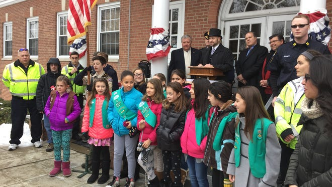 """Girl Scouts, with sign-language interpretation, sing """"The Star-Spangled Banner"""" to open the Boonton 150th birthday celebration at Town Hall on March 18, 2017."""