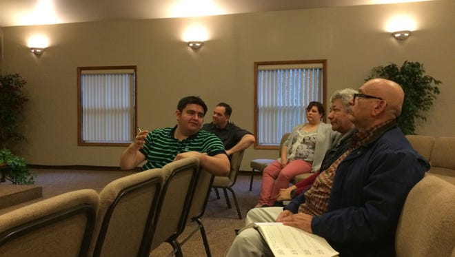 Eric Hernandez, left, interprets a discussion about police and immigrants to Gonzalo and Marie Quezada during a meeting Friday evening at Church at Wazeecha, 8016 Portage County FF, Kellner.