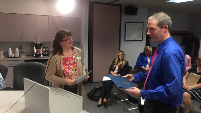 Plymouth-Canton Board of Education Trustee Patricia Mullen, here presenting an award to chemistry teacher Scott Milam, announced her resignation from the board, effective Dec. 10.