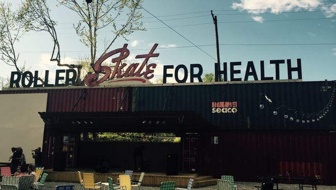 The backyard stage at Railgarten incorporates a vintage sign from the former Skateland Rink on Summer Avenue.