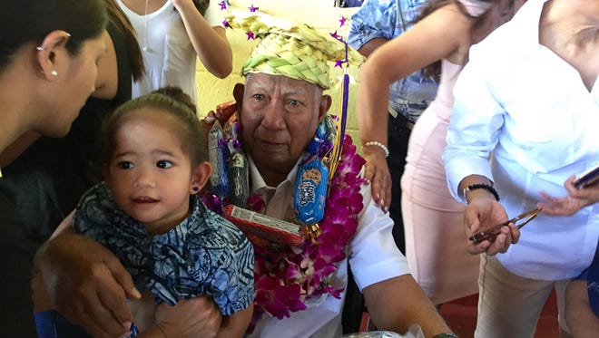88-year-old Jesus C. Babauta is about to have a photo with one of his 48 great-grandchildren, 2-year-old Keianna Castro, moments after Babauta received on Thursday an honorary high school diploma 71 years later.