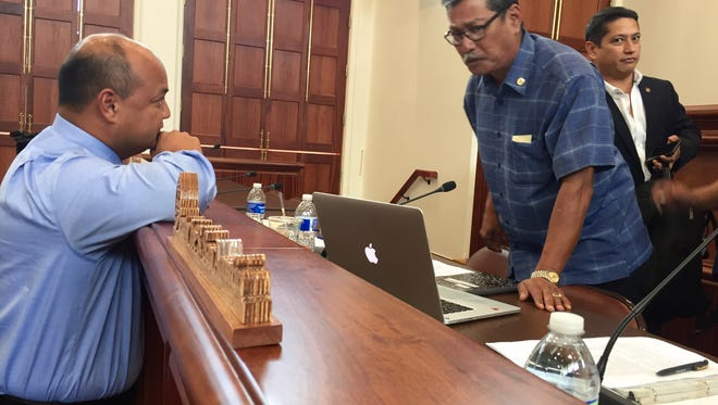 Education Superintendent Jon Fernandez, left, confers with Sen. Joe San Agustin, right, during a meeting on the Guam Department of Education's proposed fiscal 2018 budget and other issues.