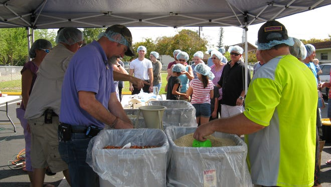 Volunteers pack meals for orphans living in the Philippines.