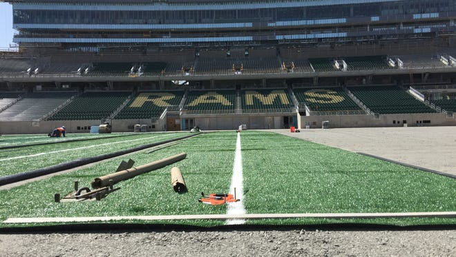 The artificial turf playing field at CSU's Canvas Stadium is being replaced at no cost to the school because of drainage issues that meet the standards required in the original construction contract, school officials said Friday.