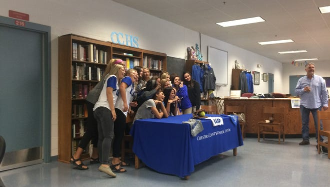 Baylee Smith and the rest of the softball team at Chester County High School line up for a picture after she signed to play with the University of Memphis on Thursday.