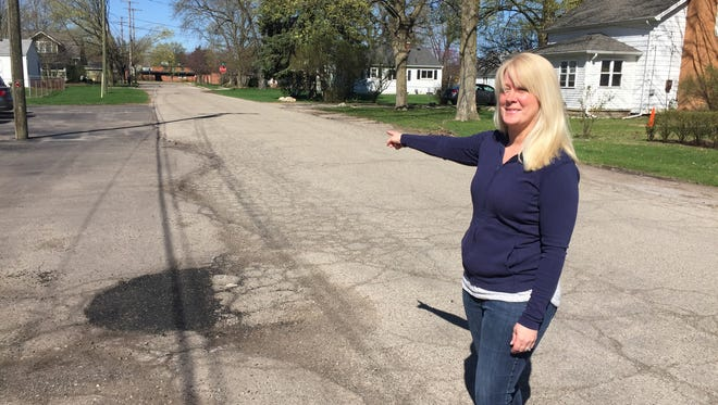 """Creative Kids Learning Center owner Jodie Hutcheson points out where her parking lot meets the edge of Chestnut Street in downtown Brighton, which leads to the back of shuttered Lindbom Elementary School. The road is one of several failed streets in the city, which has, on average, """"poor"""" roads, according to a report city officials had conducted. Road workers recently filled in a pot hole, but city officials say there is no money to replace the failed road."""
