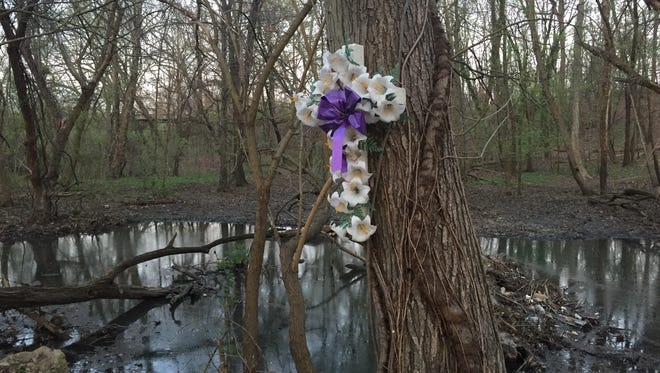 A floral wreath hangs on a tree near the site where Brendan Creato's body was found in October 2015.