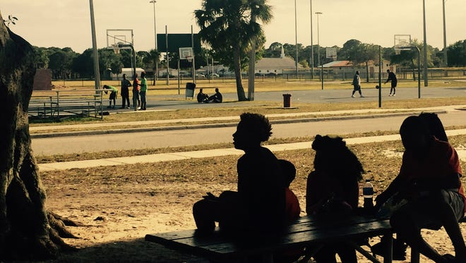 Children sit outside Lipscomb Park Community Center, a short distance away from where a shooting took place on Easter