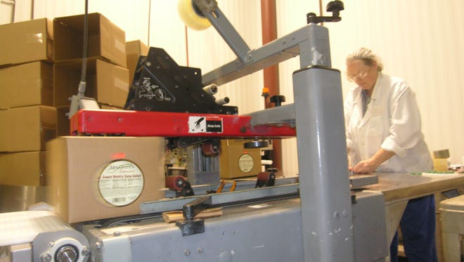 File photo 2006:  A box of tuna salad that House of Thaller employee Betty Hickman just packed zips through a taping machine and is about to go through a metal detector. Quality control is a prime concern for this Northeast Knoxville company that produces 80 containers of food per minute.