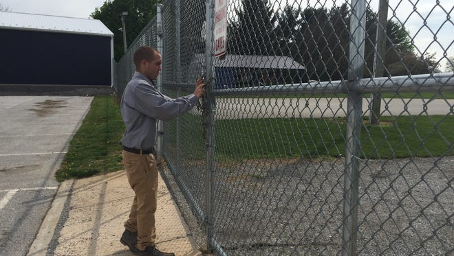 David Garabedian, zoning and codes officer for Dallastown, locks the gate to the community park. The park has been closed since April 24 because of vandalism and other problems.