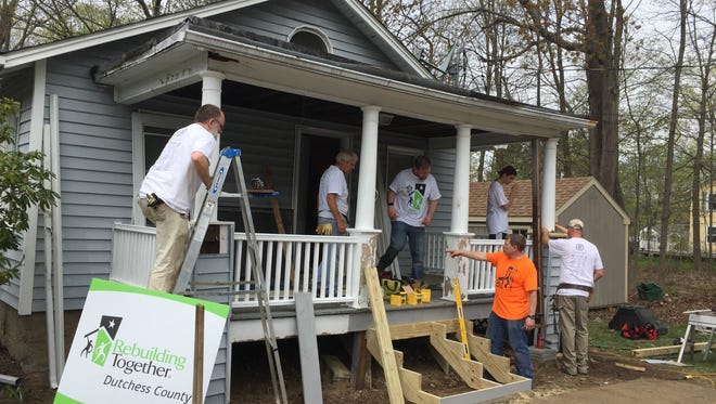 Volunteers with Rebuilding Together Dutchess County work on the Holmes home of Lynn Johnson on Saturday, April 29, 2017.
