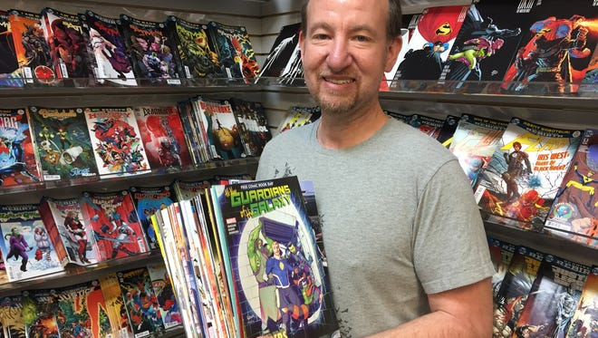 Rupp's Comics owner Chris Rupp shows off a stack of comic books that will be available free to the public this Saturday.