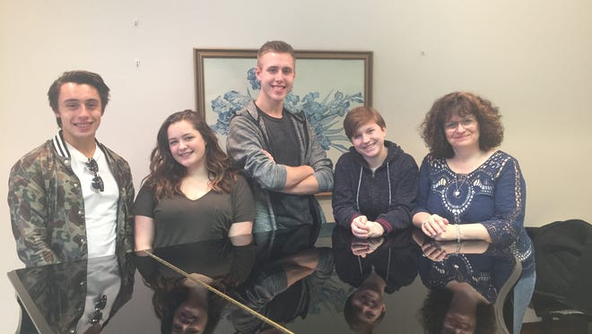 Members of the Chorolation Choir of the Wausau Conservatory of Music stand behind a piano used to rehearse. From left to right, David Livingston, 17, Lindsey Smith, 15, Will Holmson, 16, Lily Burgess, 16, and director Julie Burgess.