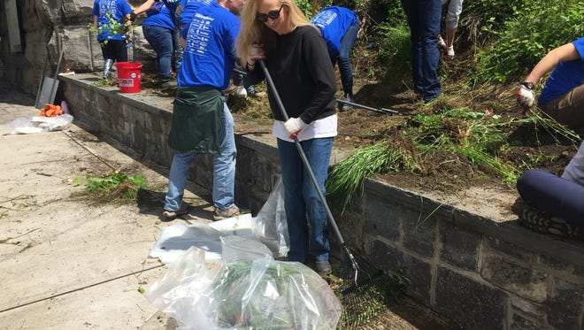 """Janet Oliver of Poughquag, with rake, was one of numerous volunteers who participated in """"I Love My Park Day"""" at Walkway Over the Hudson State Historic Park in Poughkeepsie in this 2017 file photo."""