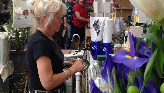 Chere Bergau, owner of Swonk's Flower Shop, works on floral arrangements Tuesday during the Mother's Day rush.