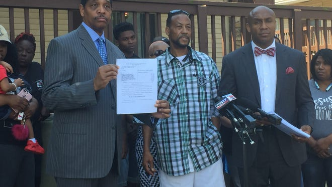 Attorneys Robert Spence, left and Mawuli Davis show the lawsuit filed in Circuit Court Tuesday while surrounded by Jalen Johnson Milan's family.