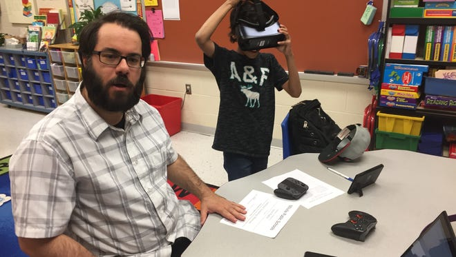 """Aaron Righter, a technology teacher at Millville Memorial High School, introduced visitors  to the Student Learning and Technology Showcase on Thursday to computer-related course offerings. Asaias Johnson, 10, who attends R.D. Wood Elementary School puts on a virtual reality headset Righter brought along as """"flash."""" The annual showcase was hosted by Holly Heights Elementary School."""