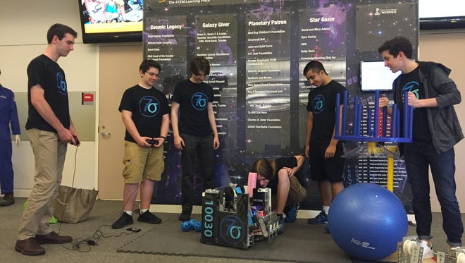 Members of 7 Sigma FTC 10030 demonstrate the functionality of the robot used for last season's competition.