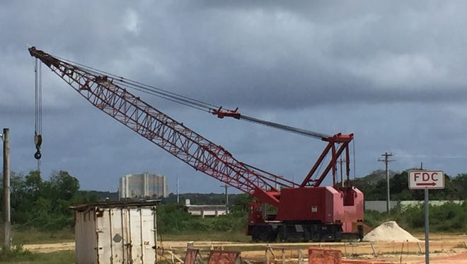 A mobile crane on Monday sits at the Tiyan site where a new warehouse will be built for the Department of Education.