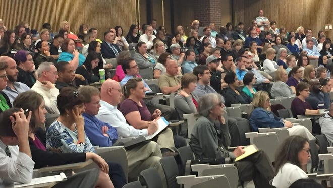 A crowd of faculty, staff and students listen to Eastern Michigan University administrators discuss coming budget cuts