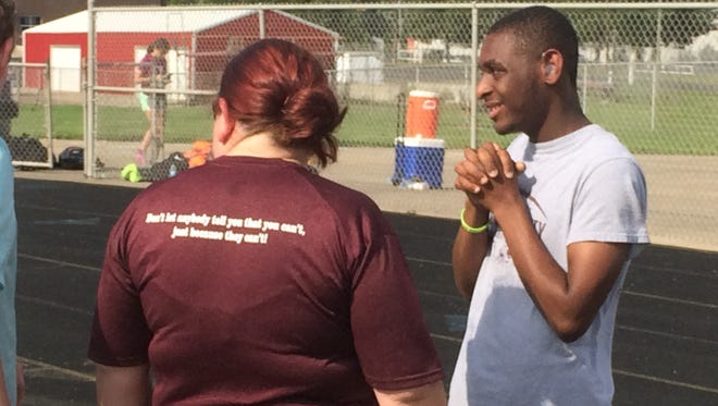 Henderson County senior Savion Whitlock talks with some of his teammates and assistant coach Jennifer Connell during practice on Thursday at Henderson County High School. Whitlock will be competing in the Unified 2x50-meter dash at the the KHSAA state track meet Saturday in Lexington.