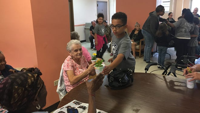 Silver Run Elementary School student Caleb Garrison distributes potted flowers Monday morning in the community room at Riverview West high-rise.