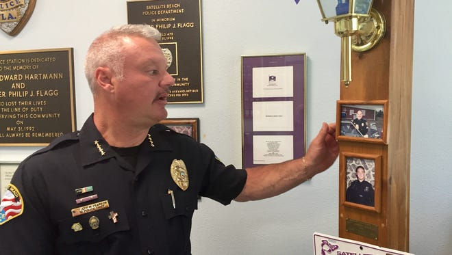 Satellite Beach Police Chief Jeff Pearson discusses Sgt. Ed Hartmann and Officer Philip Flagg in the police department lobby.