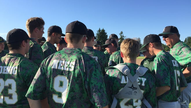 Regis players meet with head coach Don Heuberger after Friday's 5-0 victory over Oakland in the 2A/1A quarterfinals.