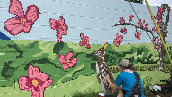 Artist Emily Clanton works on a mural she designed. The mural was a joint project between Clanton and a Furman University May ex art class. May 30, 2017