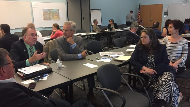 A group of staff members from the cities of Loveland and Fort Collins and Larimer County discuss at a regional meeting Wednesday night in Loveland at the city's Public Works building the county's mental health ballot measure that failed last November. Front, from left: Larimer County Business Analyst Drew Davis, city of Loveland Public Works Director Leah Browder and city of Loveland Community Partnership Office administrator Alison Hade. Back: Loveland City Manager Steve Adams, left, and Fort Collins City Manager Darin Atteberry.