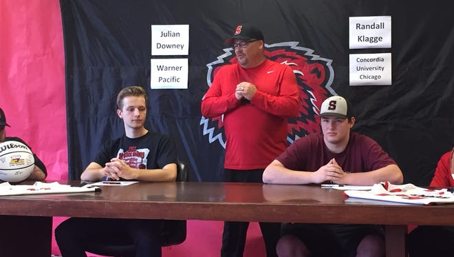 Julian Downey (left), Santiam athletic director Clint Forste (center) and Randall Klagge during a signing day ceremony at Santiam High School on June 1, 2017.